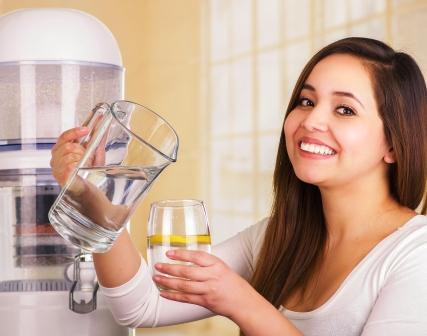 žena nalieva vodu s džbanu do pohára