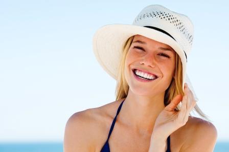 žena v plavkách, s klobúkom na hlave sa usmieva