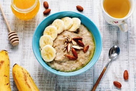 Miska ovsenej kaše s platkami bananov, mandli, slnecnicovych semien a s medom