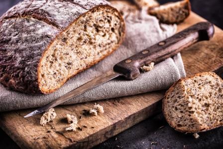 celozrnný chlieb na podložke a odkrojený krajec chleba