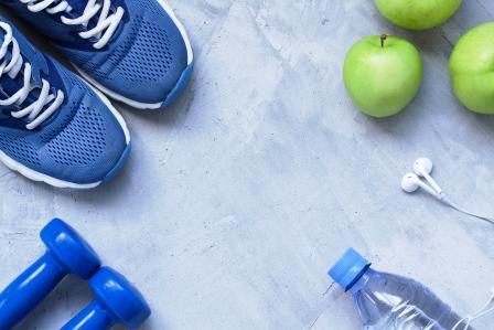 koncept zdravého životného štýlu - tenisky, činky, voda a jablká