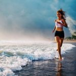 mladá žena športuje na pláži - beh