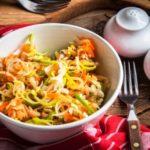 salat s porkom, mrkvou a jablkami na drevenom stole