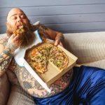 tuk na bruchu, tučný lenivý muž je pizzu na gauči