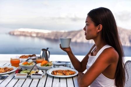 zena pije kavu pri pohlade na more